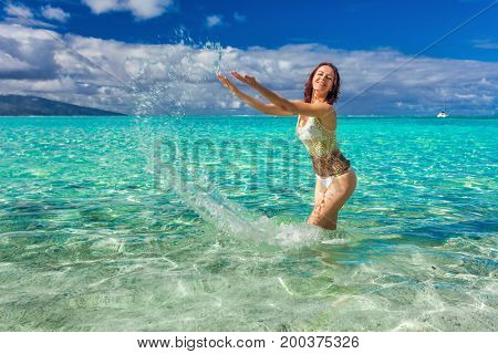 Young fit and smiling woman having fun on the tropical beach