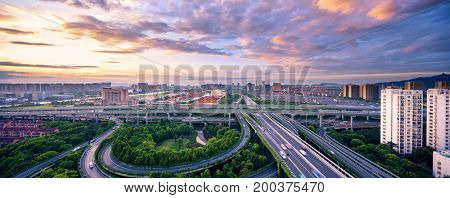 busy traffic on road junction in midtown of hangzhou in colorful cloud sky from top view