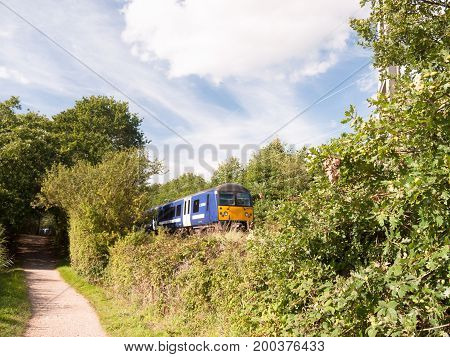 Countryside Scene Walking Trail Next To Train Track With End Of Train Going By Out Of Focus