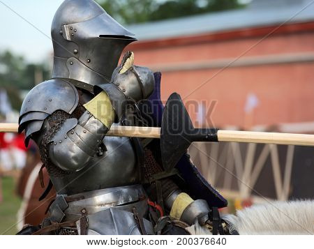 ST. PETERSBURG, RUSSIA - JULY 9, 2017: Armored knight on a horse participating in the jousting tournament during the military history project Battle On Neva at St. Peter and Paul fortress