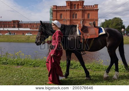 ST. PETERSBURG, RUSSIA - JULY 8, 2017: Women in medieval clothes prepares a horse for jousting during the military history project Battle On Neva. The main event this year is jousting tournament