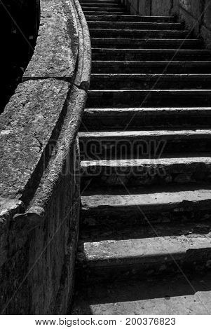 Grayscale image of old Stone stairway in an antique architecture under sunlight
