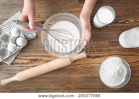 Elderly woman making dough in bowl on table
