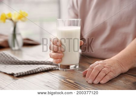 Old woman holding glass with fresh milk over table