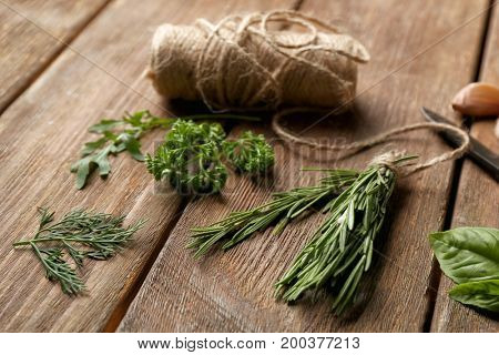 Composition with fresh herbs on wooden background