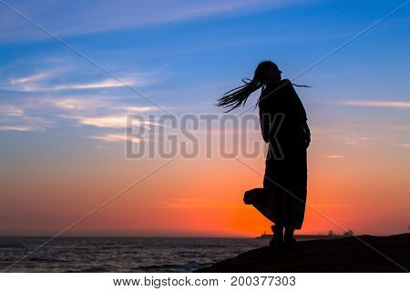 Silhouette woman on the sea beach at amazing sunset.