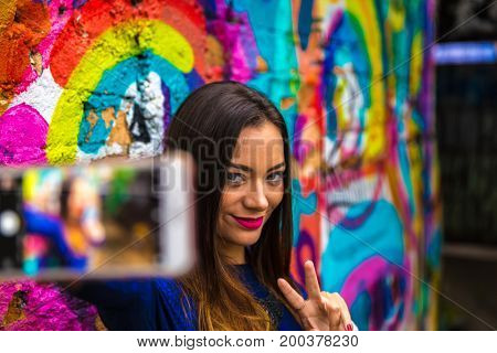 Fashion pretty carefree woman taking selfie photos in colorful abstract background