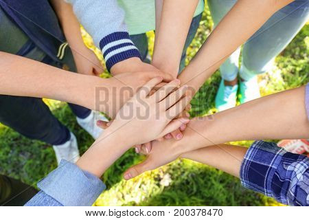 Young people putting hands together outdoors. Volunteer concept