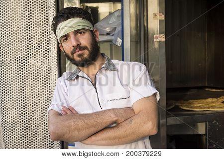 Tehran IRAN - August 16 2017 Bakery worker portrait standing in front of bakery shop.