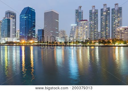 Night city building with water reflection at twilight cityscape downtown background
