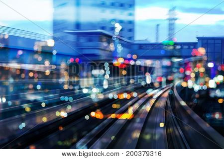 Night blurred bokeh light city downtown over motion blurred of train moving abstract background