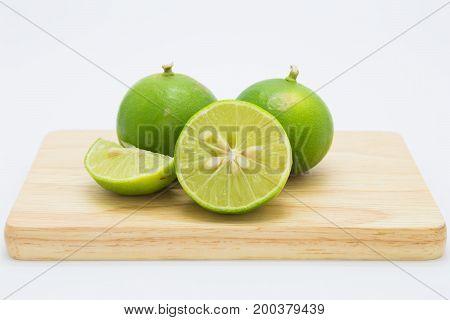 Green slide limes on wooden borad on white background