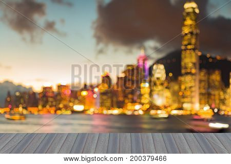 Opening wooden floor Hong Kong city night blurred bokeh light over Victoria bay abstract background