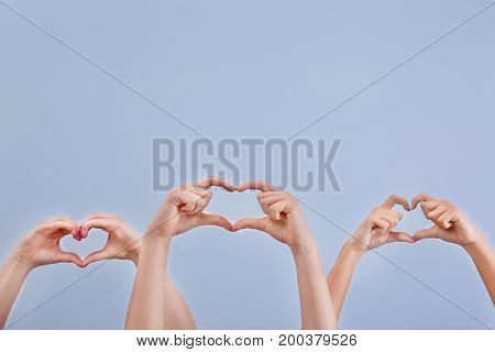 Hearts made by raised hands on light background. Volunteering concept