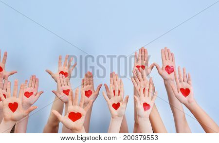 Raised in air hands with drawn hearts on palms against light background. Volunteering concept