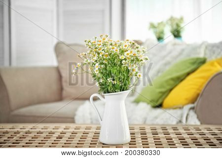 Beautiful chamomiles in white jug on table