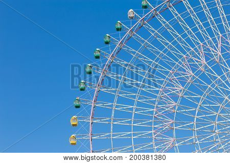 Path of funfair giant ferris wheel with clear blue sky background