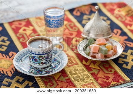 Turkish coffee with glass of water and turkish delights on traditional table cloth in warm colors