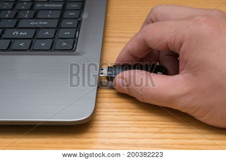 hand putting a USB flash drive to a laptop