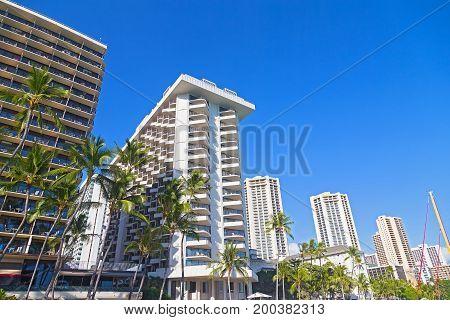 Waikiki beach waterfront buildings under tropical blue sky Hawaii USA. Modern buildings on a street with tall palm trees.