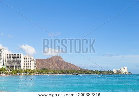Waikiki beach and Diamond Head mountain Hawaii USA. Vacationers in waters of a popular beach on tropical island.