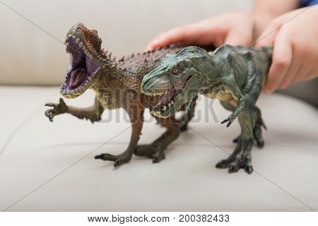 kids hands catching a brown Carcharodontosaurus and a green tyrannosaurus toy on a sofa at home