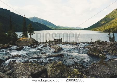 River flow with huge stone. The river flows into the Multinskoe lake. Noise between the two lakes. Altay Russia