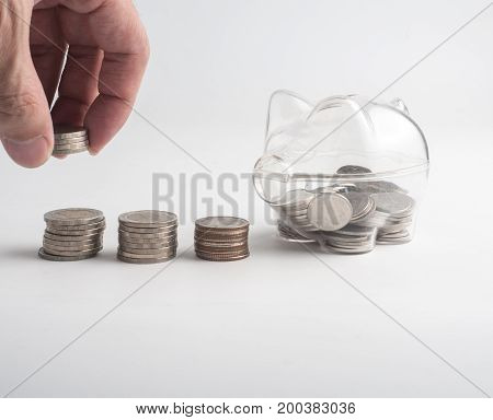 stack of money safe.Hand putting coin into stack.transparent see through piggy bank filled with coins on white background.
