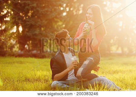 A loving couple of teenagers. Sudden picnic in the park at sunset. Teens drink soft drinks sitting on the lawn. They look into each other's eyes.