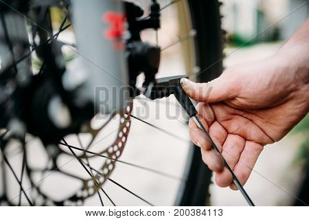 Bicycle mechanic hands adjusts disk brakes