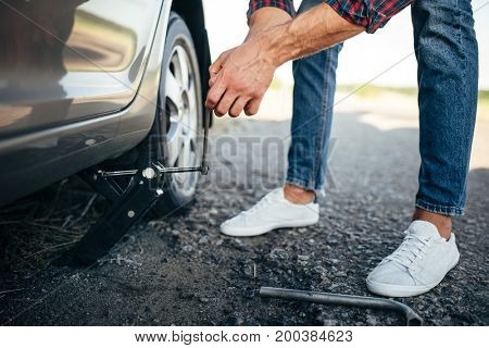 Man jack up broken car, wheel replacement
