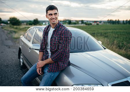 Smiling man near his car on roadside in summer day