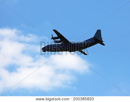 Four-engine military transport aircraft in flight in cloudy sky