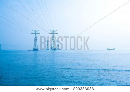 High-voltage power transmission towers in the sea skyline