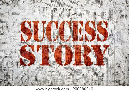 success story sign painted in stencil font on an old, grunge stucco texture wall