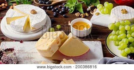 Cheese With Grapes And Nuts  On  Dark Wooden Table.