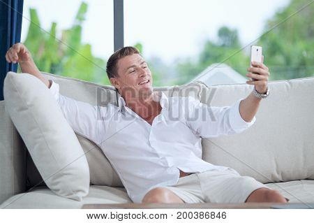 portrait of young man making self photo with his mobile phone
