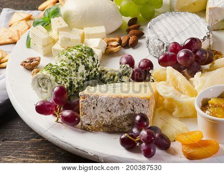 Cheese Plates Served With Grapes, Jam,  And Nuts On A Wooden Board.
