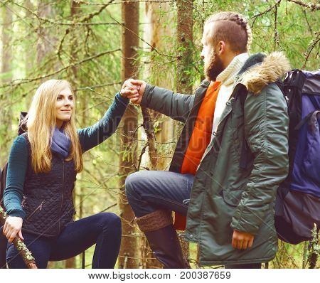 Friends walking in forest and enjoying a good autumn day. Camp, holiday, adventure, trip, hiking concept.
