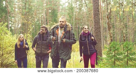 Young happy friends walking in forest and enjoying a good autumn day. Camp, tourism, hiking, trip, concept.