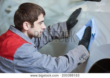 Repair man worker cleaning automobile car body in garage