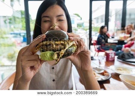 an asian young woman enjoy eating a balck hamburger in the restaurant