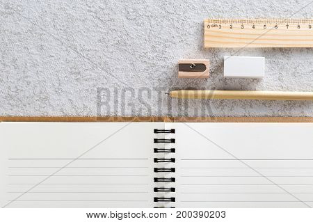 Close up of blank note book with a pen wooden pencil sharpener wooden ruler and white eraser on white cardboard background.