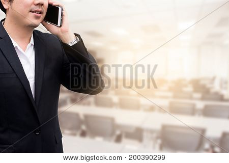 businessman using the mobile phone blurred of conference hall or seminar room.
