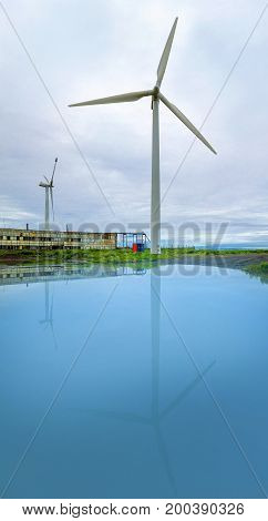 Wind power station on the shore with reflection in water