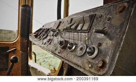 Very dirty and broken dashboard of bulldozer. Old rusty.
