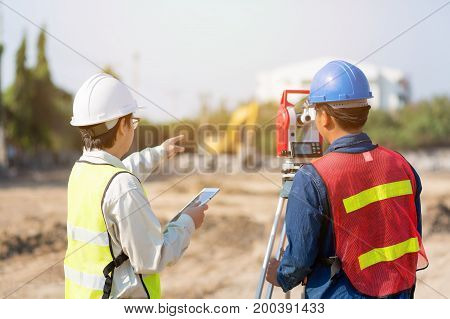 Asian Civil engineer and Asian foreman worker checking construction site for new Infrastructure construction project.