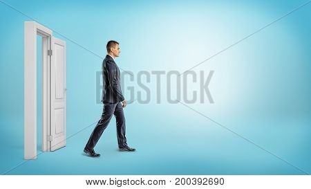 A businessman on blue background walking through an open white doorframe. New business ventures. Entering new market. Career growth.