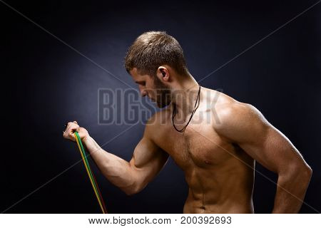 Young bodybuilder with expander on a black background . Naked torso .