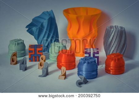 Models printed by 3d printer. Bright colorful objects printed on 3d printer on table.Automatic three dimensional printer performs plastic modeling in laboratory. Progressive modern additive technology